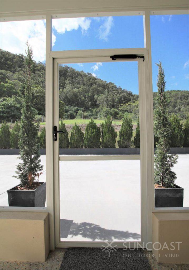 White swing screen door on patio enclosure